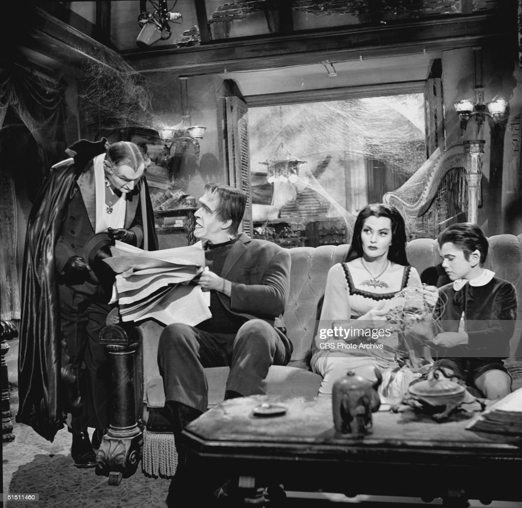 American actor and children's book author Fred Gwynne (1926 - 1993) (as Herman Munster) holds a newspaper and talks to Al Lewis (as Grandpa) while Canadian actor Yvonne de Carlo (as Lily Munster) and child actor Butch Patrick (as Eddie Munster) sit beside Herman on a couch and pretend to busy themselves while they secretly listen to the two men speak in a still from the CBS television situation comedy 'The Munsters' episode 'Grandpa Leaves Home,' November 11, 1964. The episode first aired December 24, 1964. A boom microphone is visible at top right.