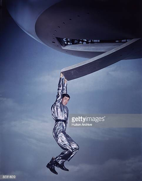 American actor and comedian Jerry Lewis hangs from a spaceship in a silver spacesuit in a promotional portrait from director Norman Taurog's film...