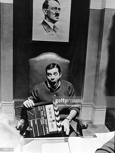 American actor and comedian Jerry Lewis sits open mouthed below a picture of Adolf Hitler and holds a film clapper on the set of the film 'The Day...