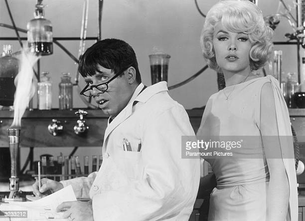 American actor and comedian Jerry Lewis wearing a lab coat and glasses as actor Stella Stevens poses next to him in a still from Lewis's film 'The...