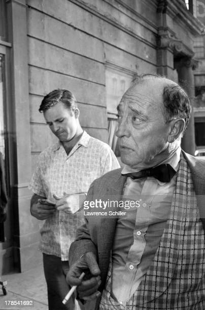 American actor and director Buster Keaton smokes a cigarette during a break in the filming of an unidentified television program Culver City...