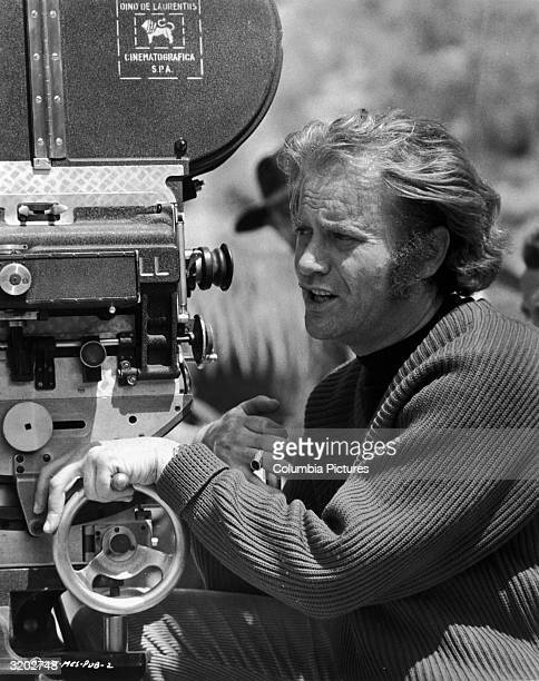 American actor and director Vic Morrow squints while standing behind a motion picture camera outdoors on a film set