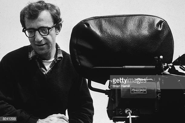 American actor and director Woody Allen smiles next to a movie camera on the set of his film 'Annie Hall'