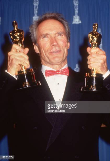 American actor and film director Clint Eastwood holds up his two Oscars for Best Director and Best Actor for his film 'Unforgiven' in front of a blue...