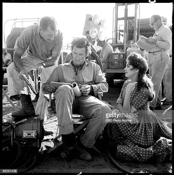 American actor and later director Clint Eastwood reads a script while director James P Yarbrough talks to him and costar Karen Sharpe who sits next...