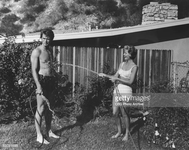 American actor and later director Clint Eastwood's wife Maggie sprays him with a garden hose as they stand about in bathing suits in the backyard of...