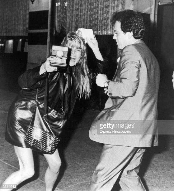 American actor and model Christie Brinkley takes pictures with a Polaroid camera as her boyfriend American singer and songwriter Billy Joel looks on...