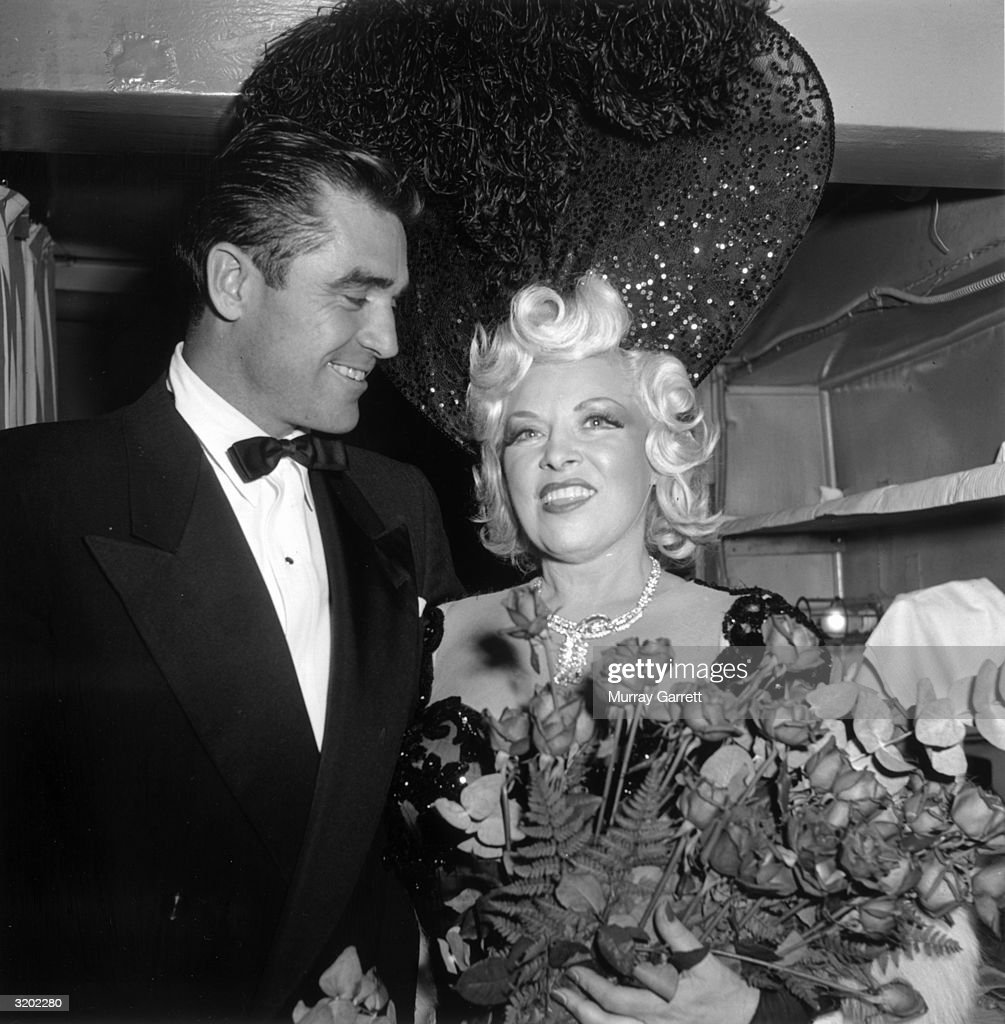 American actor and playwright Mae West smiles with actor Steve Cochran while holding a bouquet of roses at the Peppermint West nightclub, Hollywood, California. West wears a large sheer sequined headdress trimmed with ostrich feather plumes.