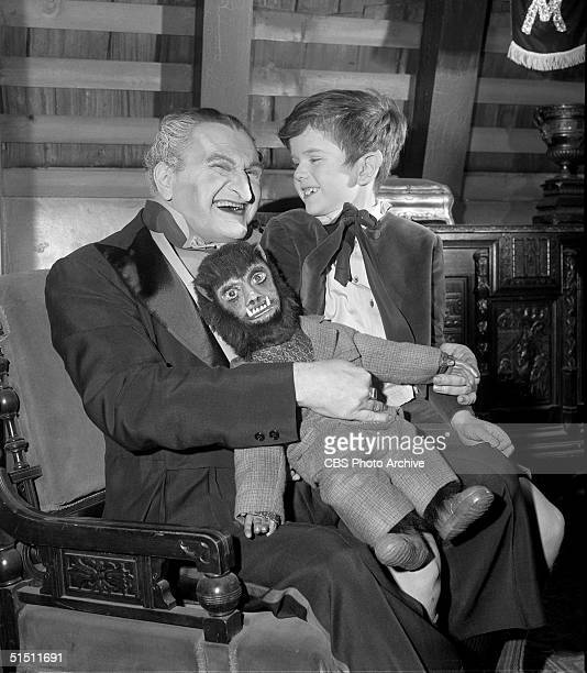 American actor and political activist Al Lewis sits and holds child actor Butch Patrick and a wolfman doll in his lap on the set of the CBS...