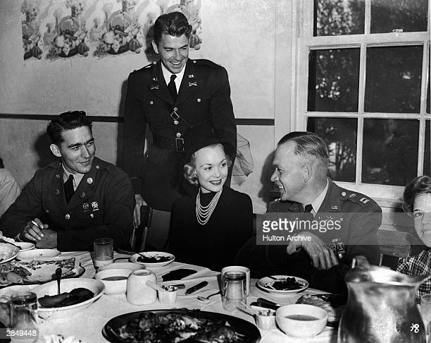American actor and politician Ronald Reagan stands behind his wife actor Jane Wyman who sits down to dinner circa 1940s She is seated between two...