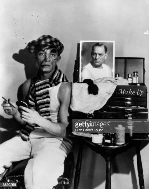 American actor and silent film comic Buster Keaton made up to look like a tough guy while a photograph of Lon Chaney appears to watch him