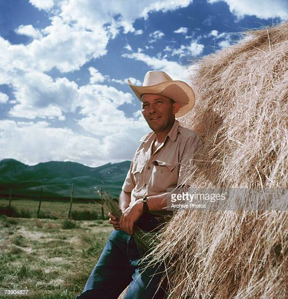 American actor and singer Bing Crosby leans dreamily against a haystack circa 1955