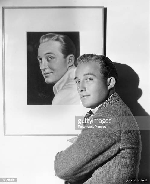 American actor and singer Bing Crosby mimicking a framed portrait of himself on the wall