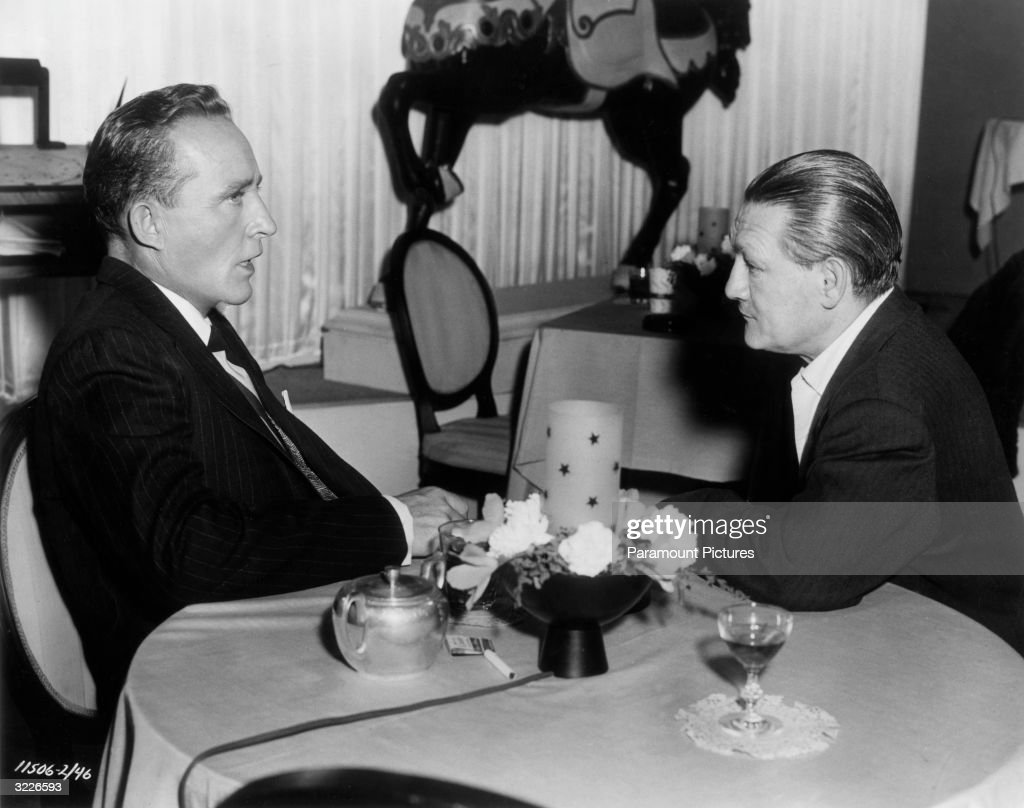 American actor and singer Bing Crosby (L) talking to American composer and conductor Victor Young on the set of director Michael Curtiz's film, 'White Christmas'. Young was visiting the set in order to discuss a recording date with Crosby.