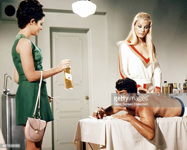 American actor and singer Dean Martin receives a bottle of whisky from actress Beverly Adams during a massage in a scene from the comedy film 'The...