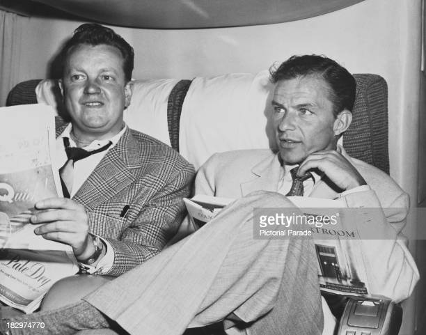 American actor and singer Frank Sinatra with scriptwriter Paul Dudley on board an American Overseas Airlines Boeing 377 Stratocruiser during a flight...