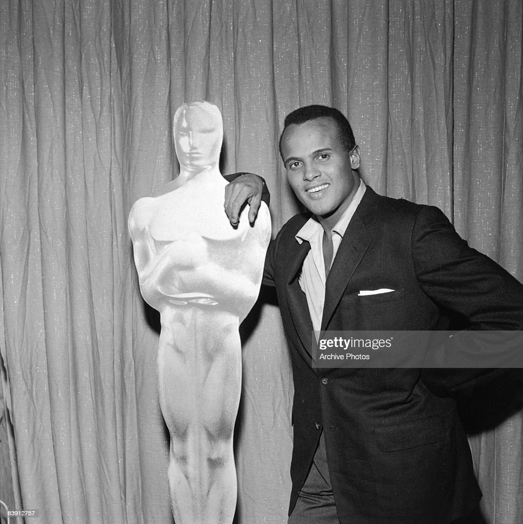 American actor and singer <a gi-track='captionPersonalityLinkClicked' href=/galleries/search?phrase=Harry+Belafonte&family=editorial&specificpeople=204214 ng-click='$event.stopPropagation()'>Harry Belafonte</a> leans against an Oscar statue at the Academy Awards, 27th March 1956.