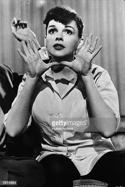 American actor and singer Judy Garland holds her hands up near her face circa 1950s