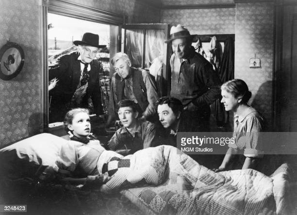 American actor and singer Judy Garland sits up in bed while Frank Morgan Charles Grapewin Ray Bolger Jack Haley Bert Lahr and Clara Blandick surround...