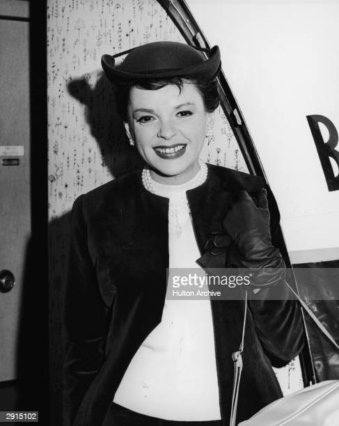 American actor and singer Judy Garland smiles and boards a plane en route to London to attend the premiere of her film 'I Could Go on Singing'...