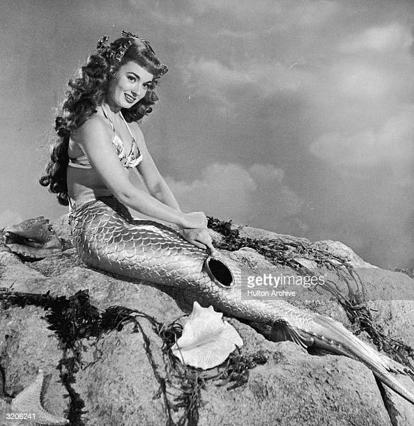 American actor Ann Blyth wearing a mermaid costume sits on a rock in a promotional portrait for director Irving Pichel's film 'Mr Peabody and the...