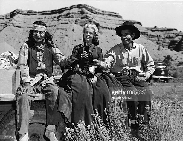 American actor Arlene Dahl drinks CocaCola with two American Indian actors in costume on the location set of the Western film 'The Outriders'...