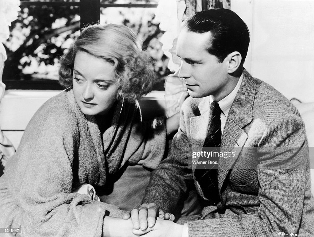 American actor <a gi-track='captionPersonalityLinkClicked' href=/galleries/search?phrase=Bette+Davis+-+Actress&family=editorial&specificpeople=93133 ng-click='$event.stopPropagation()'>Bette Davis</a> (1908 - 1989) looks away as she holds hands with American actor <a gi-track='captionPersonalityLinkClicked' href=/galleries/search?phrase=Franchot+Tone&family=editorial&specificpeople=214212 ng-click='$event.stopPropagation()'>Franchot Tone</a> (1905 - 1968) in a still from director Alfred E Green's film 'Dangerous.'
