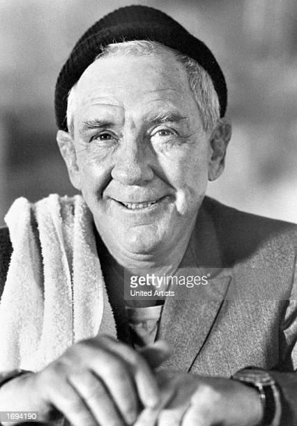 American actor Burgess Meredith wears a hat and a towel over his shoulder in a promotional portrait for the film 'Rocky' directed by John G Avildsen...