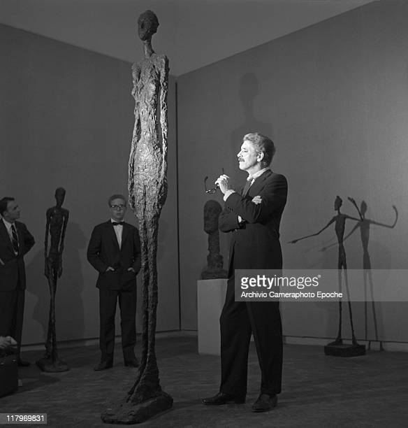 American actor Burt Lancaster wearing a pinstriped suit and a tie holding glasses portrayed while standing in front of Alberto Giacometti's sculpture...