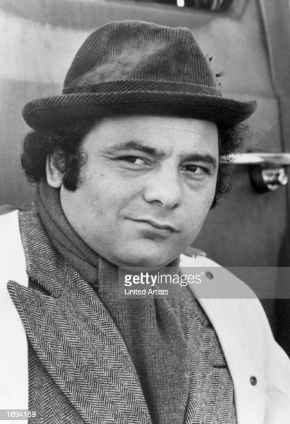 American actor Burt Young wears a hat and scarf with a tweed jacket outdoors in a headshot still from the film 'Rocky' directed by John G Avildsen...