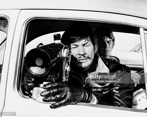 American actor Charles Bronson as Arthur Bishop in 'The Mechanic' directed by Michael Winner 1972 Behind him is JanMichael Vincent as Steve McKenna