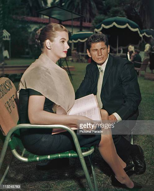 American actor Charles Bronson learning his lines with wife Jill Ireland on a film set circa 1970