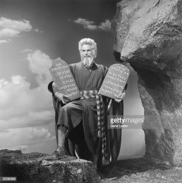 American actor Charlton Heston as Moses in a still from director Cecil B DeMille's film 'The Ten Commandments' Heston holds two stone tablets carved...