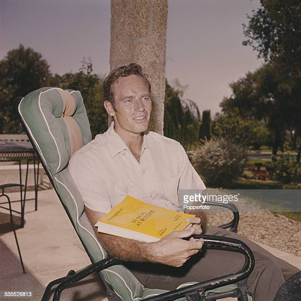 American actor Charlton Heston pictured sitting in a sun lounger chair holding the script of the film 55 Days At Peking during shooting of the film...