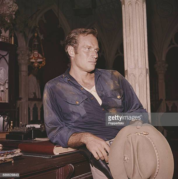 American actor Charlton Heston pictured standing at a desk in a gothic style interior in Spain during shooting of the film 55 Days At Peking in 1962
