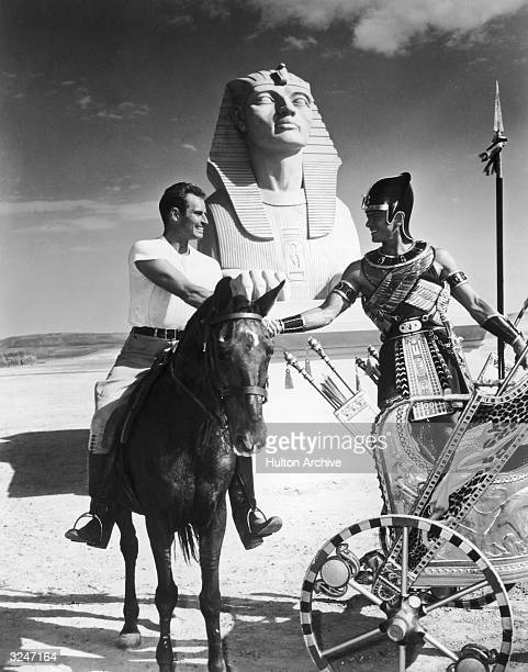 American actor Charlton Heston rides on horseback while shaking hands with Russianborn actor Yul Brynner who stands in a chariot prior to the filming...