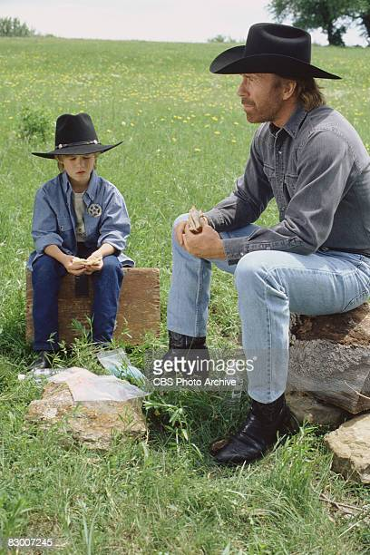 American actor Chuck Norris and Haley Joel Osment sit outdoors in a scene from an episode the television series 'Walker Texas Ranger' entitled...