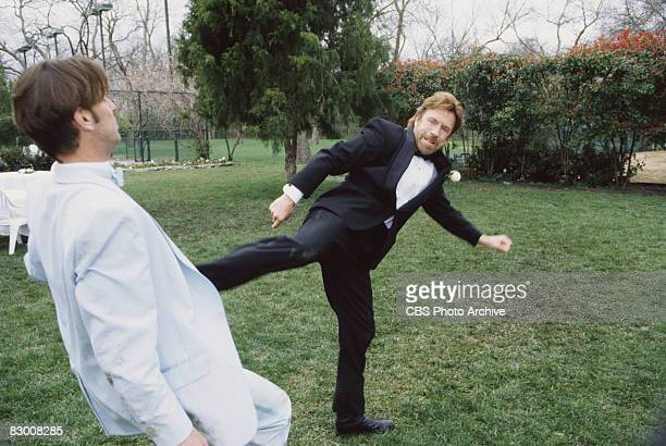 American actor Chuck Norris dressed in a tuxedo delivers a roundhouse kick to an unidentified actor in a scene from an episode of the television...