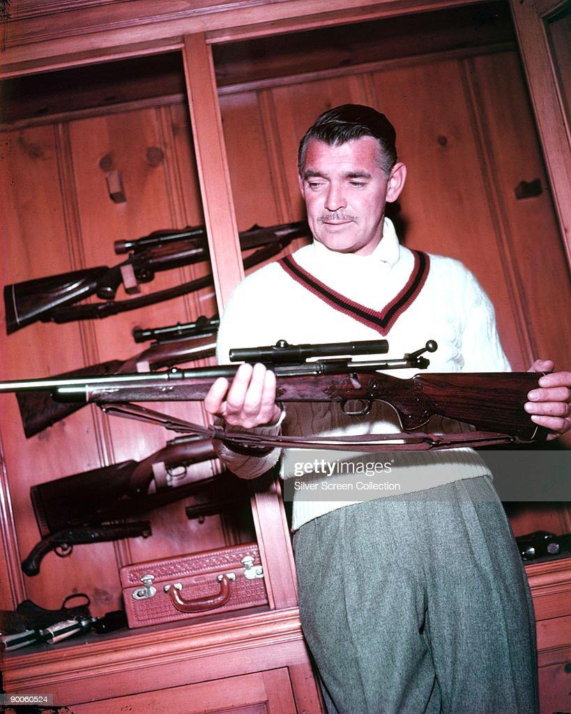 American actor Clark Gable (1901 - 1960) at home with his gun collection, circa 1950.