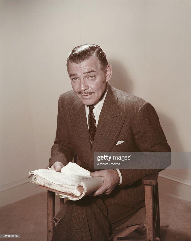 American actor Clark Gable (1901 - 1960) reading a script, circa 1955.