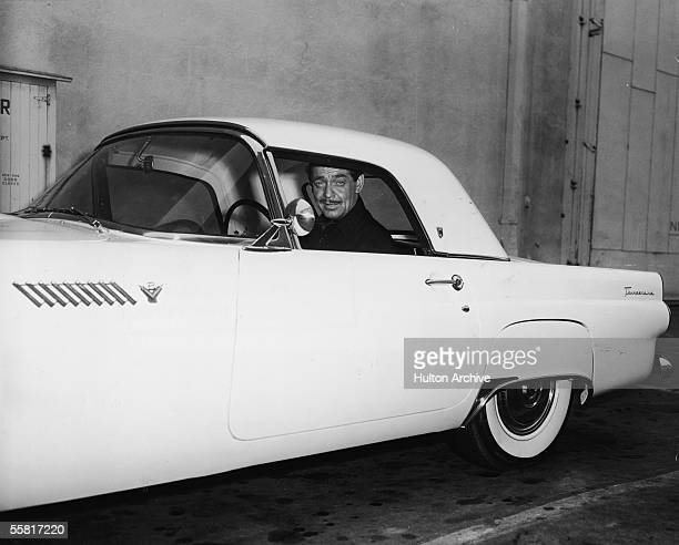 American actor Clark Gable sits in his 1955 Ford Thunderbird sports car and smiles late 1950s