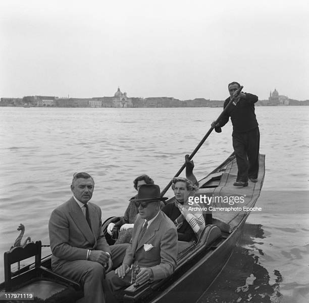 American actor Clark Gable wearing a suit and a tie sitting on a gondola with his bridetobe Kay Williams Spreckles and another couple in StMark's...