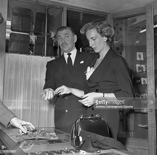 American actor Clark Gable wearing a suit and a tie standing next to his bridetobe Kay Williams Spreckles choosing a bracelet in a jeweller's on the...