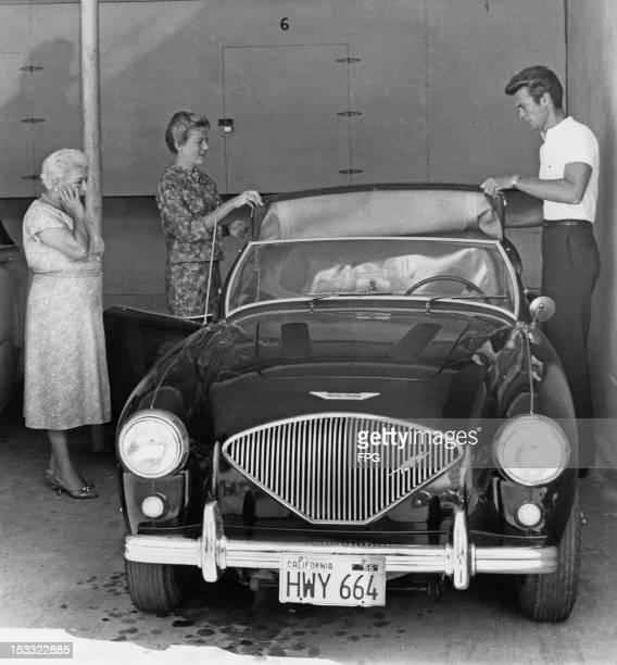 American actor Clint Eastwood and his first wife Maggie Johnson adjusting the roof of an Austin Healey sports car Hollywood California circa 1960