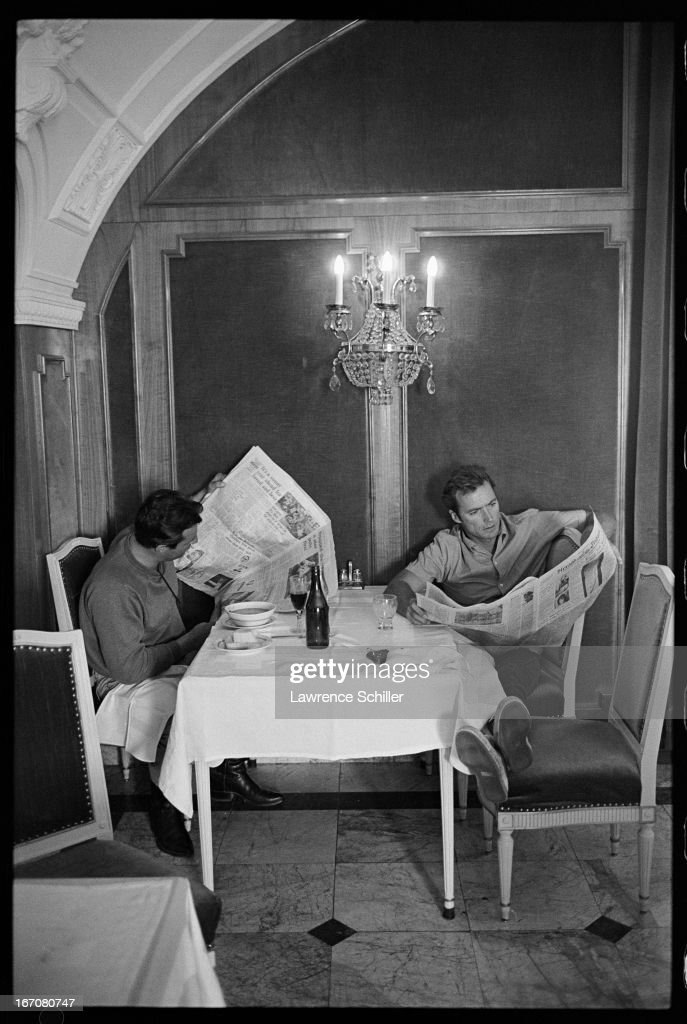 American actor Clint Eastwood and Paul Lennon read newspapers as they sit at a table during a break in filming 'Two Mules for Sister Sara' Durango...