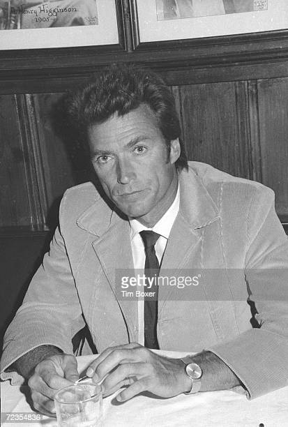 American actor Clint Eastwood dressed in a corduroy jacket plays with a book of matches as he sits behind a table at an unidentified restaurant 1969