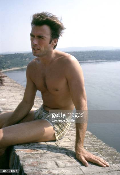 American actor Clint Eastwood dressed in a swimsuit sits on a low brick wall that overlooks an unidentified river Vizinada Yugoslavia 1969