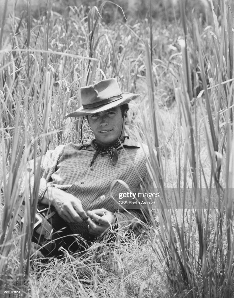 American actor Clint Eastwood smiles as he lies in tall grass for a portrait wearing a cowboy hat and Western outfit, 1961.