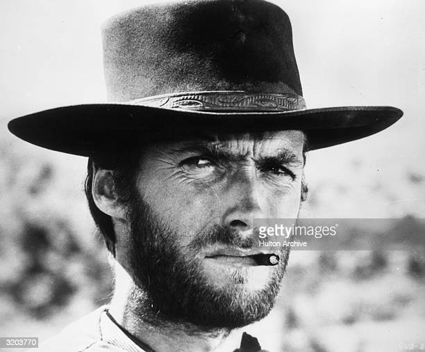 American actor Clint Eastwood squints while smoking a cigarette between his teeth in a still from director Sergio Leone's film 'The Good The Bad and...
