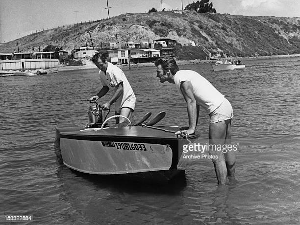 American actor Clint Eastwood with a motorboat and driver before a waterskiing session USA circa 1960